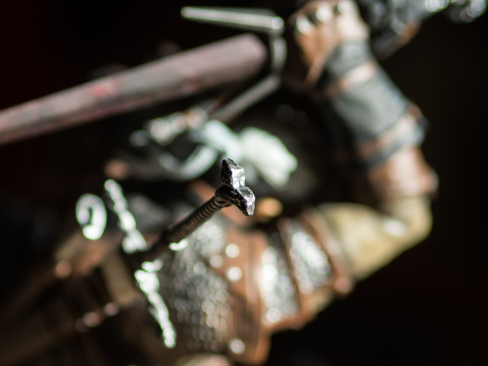 a close up of Geralts silver sword pommel from collectors edition statue