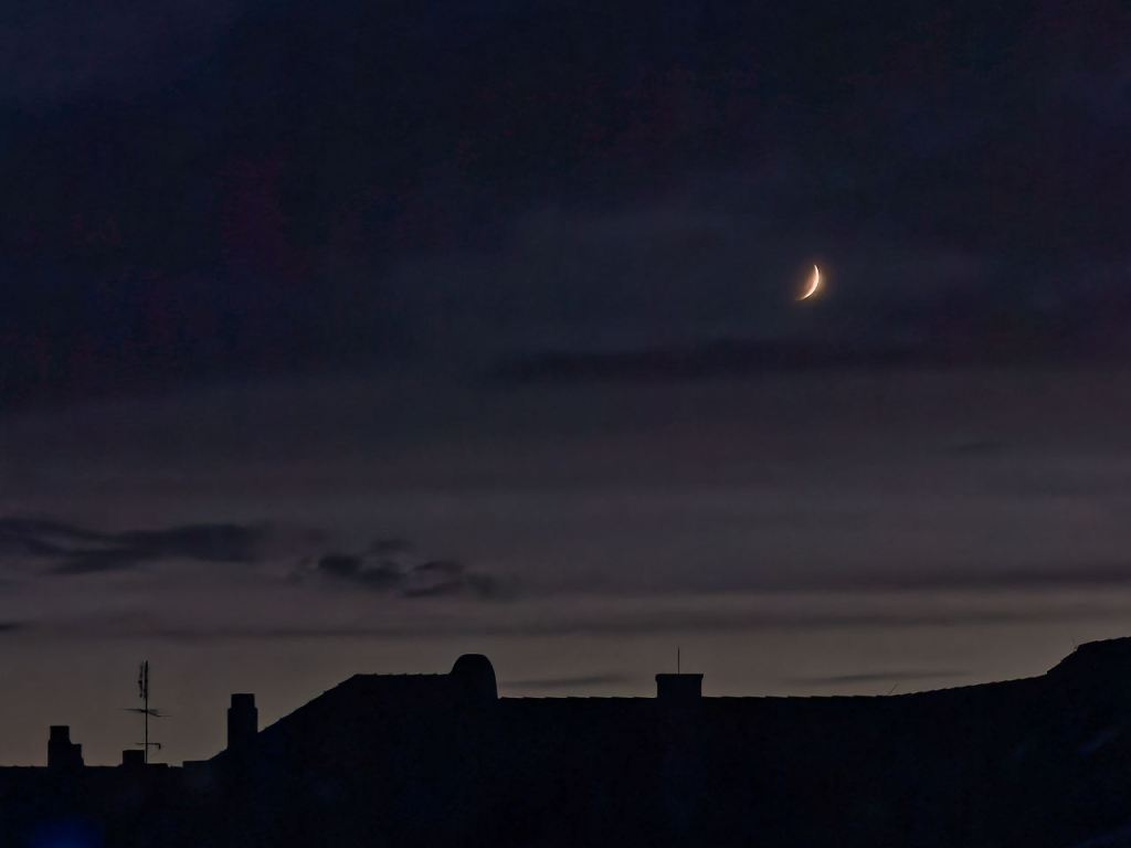 waxing crescent moon over a silhouette of rooftops